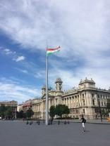 La bandera húngara junto a una hermosa edificación.